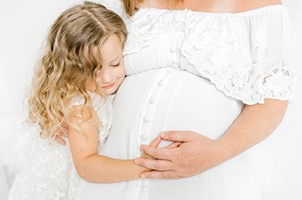 Toddler girl hugs mom's baby belly
